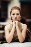 Muchacha hermosa que espera en una tabla en un café Foto de archivo libre de regalías