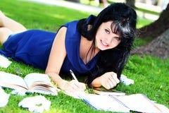 Muchacha hermosa que estudia en parque Imagen de archivo