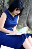 Muchacha hermosa que estudia en parque Foto de archivo