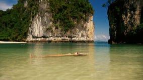 Muchacha hermosa que flota en el agua en una playa tropical almacen de video