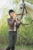 Muchacha hermosa que frota ligeramente el caballo afuera Imagen de archivo