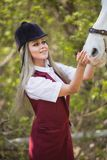 Muchacha hermosa que frota ligeramente el caballo afuera Fotos de archivo libres de regalías