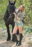 Muchacha hermosa que frota ligeramente el caballo afuera Fotografía de archivo libre de regalías
