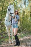 Muchacha hermosa que frota ligeramente el caballo afuera Imágenes de archivo libres de regalías