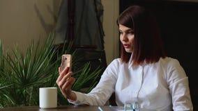 Muchacha hermosa que habla con los socios comerciales que usan una cámara del teléfono móvil almacen de video