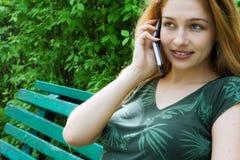 Muchacha hermosa que habla en el móvil en benc del parque Imagen de archivo