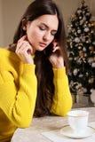 Muchacha hermosa que habla en el teléfono en el café, fondo del árbol de navidad Fotos de archivo