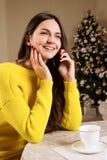 Muchacha hermosa que habla en el teléfono en el café, fondo del árbol de navidad Fotos de archivo libres de regalías