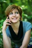 Muchacha hermosa que habla en el teléfono en el parque Imagen de archivo