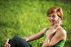 Muchacha hermosa que habla en el teléfono en la hierba Imagenes de archivo