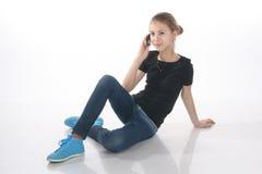 Muchacha hermosa que habla en el teléfono que se sienta en el piso Foto de archivo libre de regalías