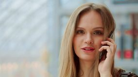 Muchacha hermosa que habla en un teléfono móvil que mira la cámara y la sonrisa Venta, consumerismo: Mujer joven con metrajes