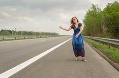 Muchacha hermosa que hace autostop en el camino Imagenes de archivo
