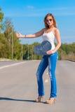 Muchacha hermosa que hace autostop en el camino Foto de archivo libre de regalías
