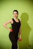 Muchacha hermosa que hace ejercicio con pesas de gimnasia rojas Foto de archivo