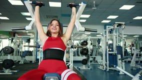 Muchacha hermosa que hace ejercicios en el dispositivo, bíceps cada vez mayor en sus manos metrajes