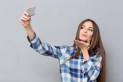 Muchacha hermosa que hace el selfie que envía un beso del aire Imágenes de archivo libres de regalías