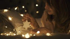 Muchacha hermosa que hace girar un juguete de la decoración del copo de nieve de la Navidad en cama Ella es feliz almacen de video