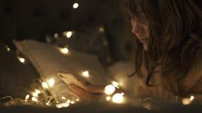 Muchacha hermosa que hace girar un juguete de la decoración del copo de nieve de la Navidad en cama Ella es feliz almacen de metraje de vídeo