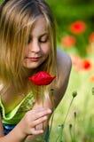 Muchacha hermosa que huele una amapola roja Fotos de archivo libres de regalías