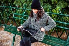 Muchacha hermosa que investiga y que sonríe con la tableta en un parque Imágenes de archivo libres de regalías