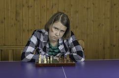 Muchacha hermosa que juega a ajedrez Imagen de archivo