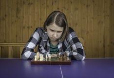 Muchacha hermosa que juega a ajedrez Imagen de archivo libre de regalías