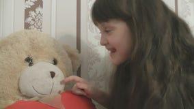Muchacha hermosa que juega con la nariz del oso de peluche metrajes