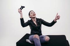 Muchacha hermosa que juega con la palanca de mando en chaqueta negra Imagenes de archivo