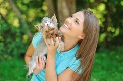 Muchacha hermosa que juega con su pequeño perrito Imagen de archivo