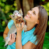 Muchacha hermosa que juega con su pequeño perrito Fotografía de archivo libre de regalías