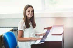 Muchacha hermosa que juega el piano en la escuela de música Imagenes de archivo