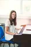 Muchacha hermosa que juega el piano en la escuela de música Foto de archivo libre de regalías