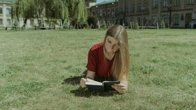 Muchacha hermosa que lee un libro en césped del campus almacen de metraje de vídeo