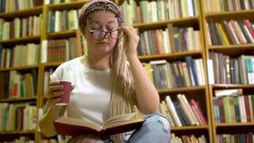 Muchacha hermosa que lee un libro en la biblioteca almacen de video