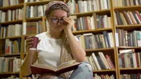 Muchacha hermosa que lee un libro en la biblioteca metrajes