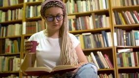 Muchacha hermosa que lee un libro en la biblioteca almacen de metraje de vídeo