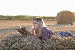 Muchacha hermosa que lee un libro en la puesta del sol en un pajar foto de archivo