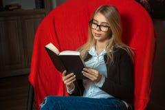 Muchacha hermosa que lee un libro en una butaca Foto de archivo libre de regalías