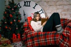 Muchacha hermosa que lee un libro que miente en el sofá Imágenes de archivo libres de regalías