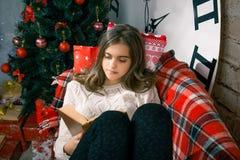 Muchacha hermosa que lee un libro que miente en el sofá Imagen de archivo