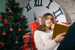 Muchacha hermosa que lee un libro que miente en el sofá Fotos de archivo libres de regalías