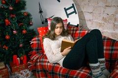 Muchacha hermosa que lee un libro que miente en el sofá Fotos de archivo