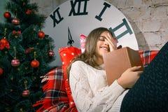 Muchacha hermosa que lee un libro que miente en el sofá Foto de archivo