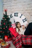 Muchacha hermosa que lee un libro que miente en el sofá Foto de archivo libre de regalías