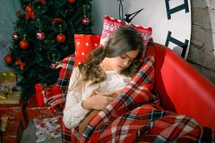 Muchacha hermosa que lee un libro que miente en el sofá Fotografía de archivo libre de regalías