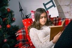 Muchacha hermosa que lee un libro que miente en el sofá Fotografía de archivo