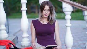 Muchacha hermosa que lee un libro que se sienta en las escaleras almacen de metraje de vídeo