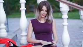 Muchacha hermosa que lee un libro que se sienta en las escaleras metrajes