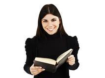 Muchacha hermosa que lee un libro y una sonrisa Foto de archivo libre de regalías